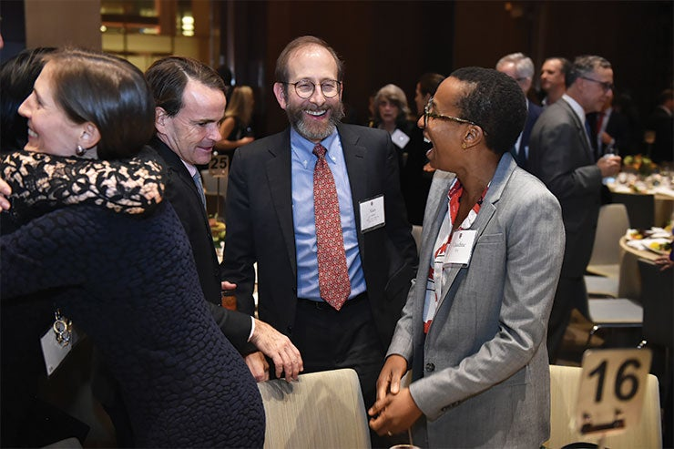 Claudine Gay and Alan Garber share a laugh at the President's Associates Dinner in 2019