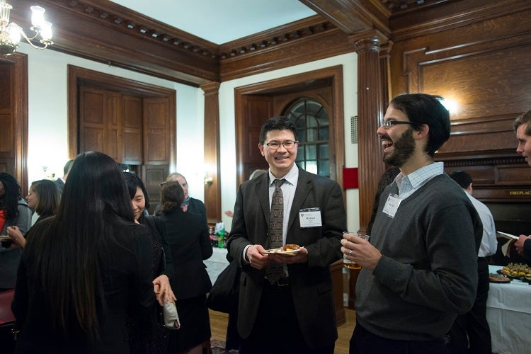 Alumni attend a reception in Phillips Brooks House.