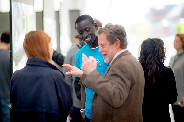 A guest interacts with students at the design fair