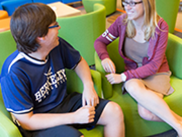 Rebekka Elizabeth-Marie Depew '16 (right) chats with a friend in the cheerful common room at Stone Hall.