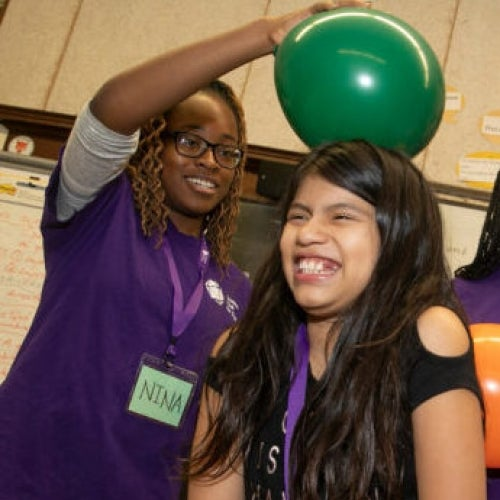 Harvard College student Nina Uzoigwe demonstrates static electricity with a balloon on the head of an Amigos School student